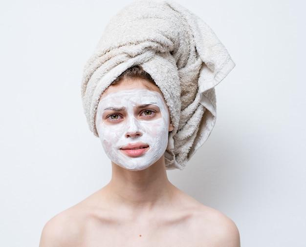Naakte vrouw met witte crème op haar gezicht en een handdoek op haar hoofd
