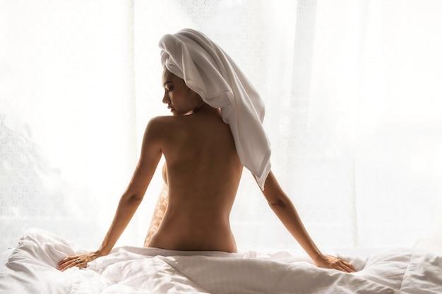 Naakte vrouw ontspannen op bed na het douchen