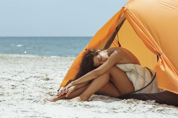 Naakte vrouw op het strand in een oranje tent