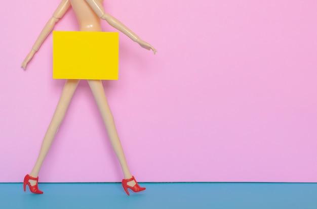 Naakte vrouwelijke pop die met rode schoen met geel document loopt dat het bodemgebied verbergt. minimaal concept van schoonheid en seksuele intimidatie.