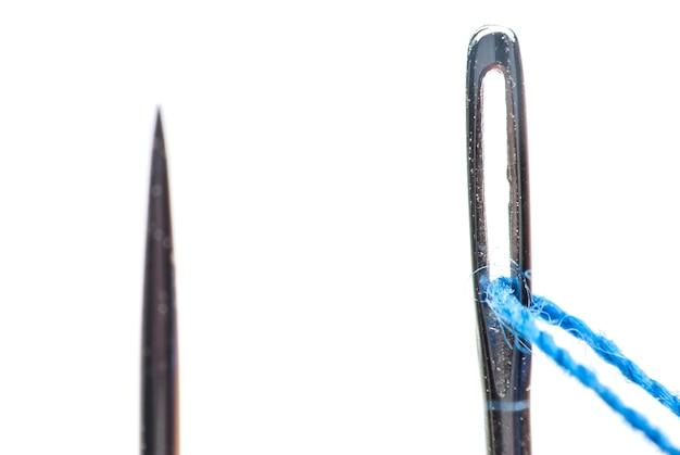 Naald en draad close-up op een witte achtergrond
