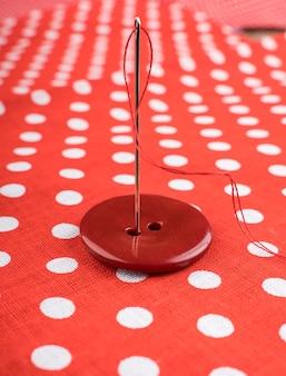 Naald in rode knop op patroonachtergrond