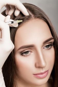 Naald mesotherapie. cosmetische is geïnjecteerd in het hoofd van de vrouw. versterken het haar en hun groei