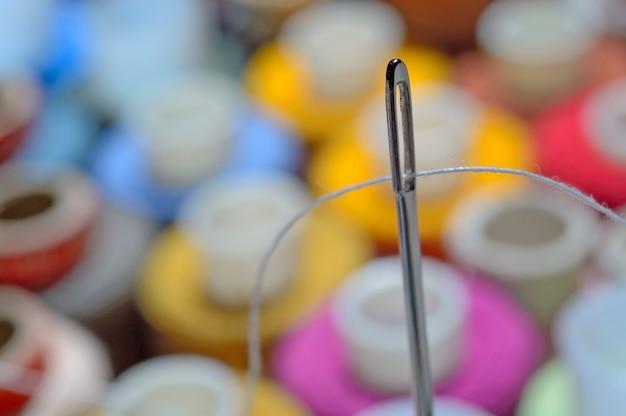 Naald met draad op een achtergrond van spoelen. detailopname. Premium Foto