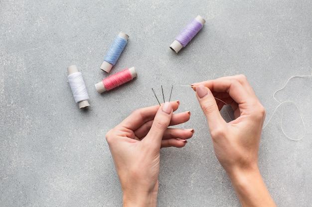 Naalden en naaigaren gebruikt door handen bovenaanzicht
