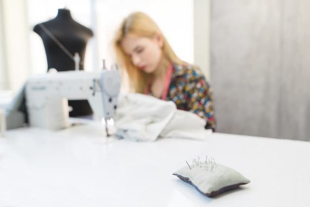 Naalden in een kussen op de achtergrond van naaisters bezig met een naaimachine
