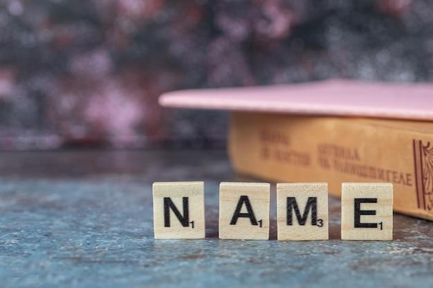 Naam schrijven met zwarte letters op houten dobbelstenen met een oud boek eromheen. hoge kwaliteit foto
