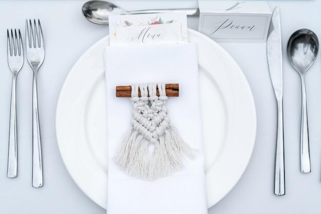 Naamkaart op een bord en een geschenk voor gasten van macrame op een stokje kaneel. decoratief item voor een bruiloftsdiner.