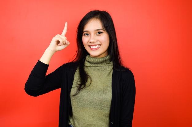Naar boven wijzend en glimlachen van jonge mooie aziatische vrouwen met zwarte trui geïsoleerd op rood