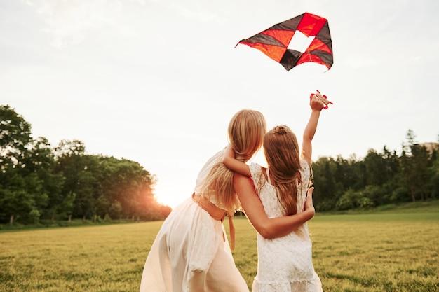 Naar de hemel kijken. moeder en dochter hebben plezier met vlieger in het veld. prachtige natuur.