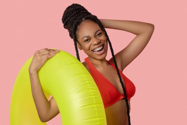 Naar het zwembad gaan. glimlachende afro-amerikaanse vrouw die een gele buis vasthoudt