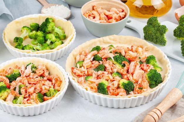 Naar huis gemaakte franse scherpe quiche met rivierkreeften en broccoli die met room en eieren worden gevuld.