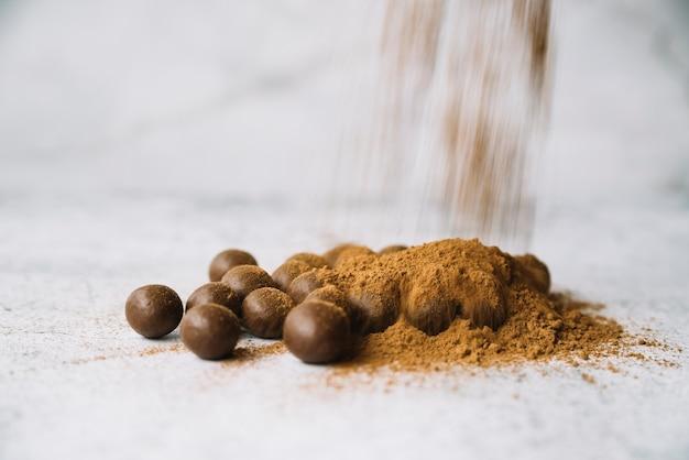 Naar huis gemaakte gezonde chocoladeballen bestrooid met cacao