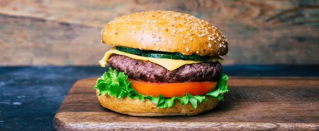 Naar huis gemaakte hamburger (cheeseburger) met rundvlees op een houten achtergrond. klassieke zelfgemaakte burger.