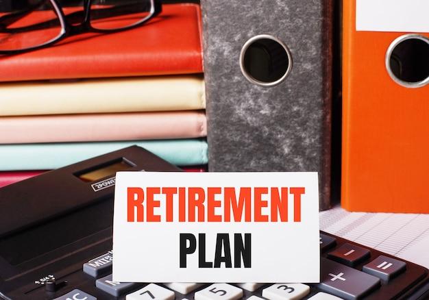 Naast de agenda's en mappen met documenten op de rekenmachine ligt een witte kaart met het opschrift pensioenplan.
