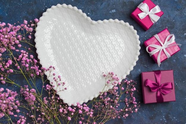 Naast de ingepakte cadeaus ligt een wit bord in de vorm van een hart en bloemen.