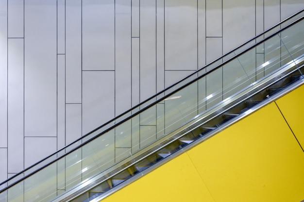 Naast gele roltrap met verlichting op muur