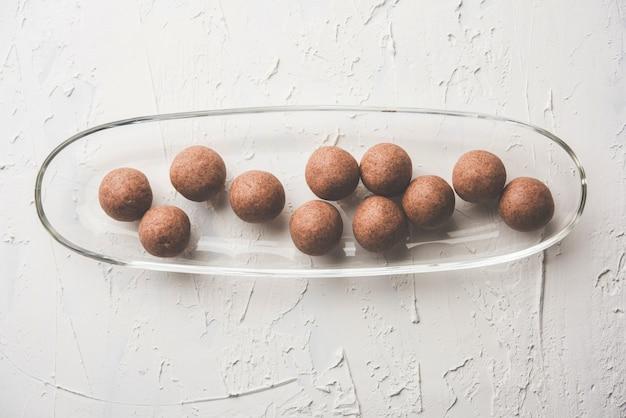 Nachni laddu of ragi laddoo of balletjes gemaakt van vingergierst, suiker en ghee. het is een gezond voedsel uit india. geserveerd in een kom of bord met rauw geheel en poeder. selectieve focus