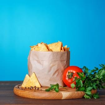 Nacho-chips in het pakket met peterselie en tomaat