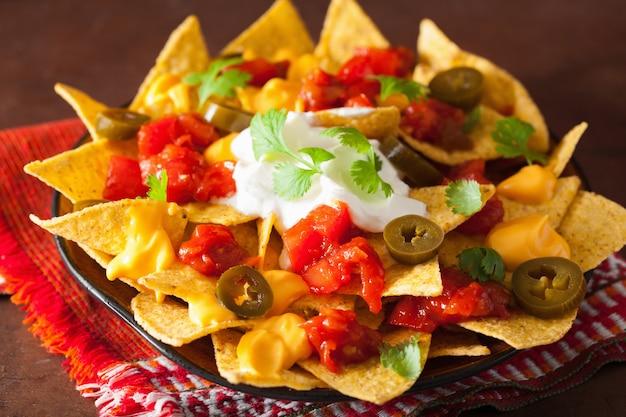 Nacho's beladen met salsa, kaas en jalapeno