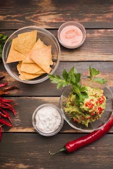 Nachos dichtbij guacamole en saus in kommen onder spaanse peper