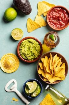 Nachos, guacamole, salsa en bier op blauwe achtergrond