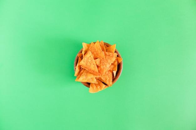 Nachos maïs chips in een houten kom op groen