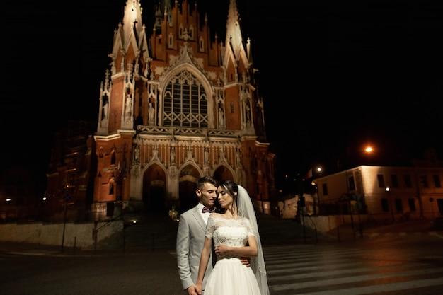 Nacht fotosessie van bruidspaar in krakau, newlyweds lopen rond de kerk