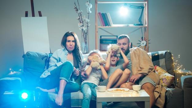 Nacht. gelukkige familie die 's avonds thuis naar projector, tv, films met popcorn en drankjes kijkt. moeder, vader en kinderen brengen samen tijd door. thuiscomfort, moderne technologieën, emotiesconcept.
