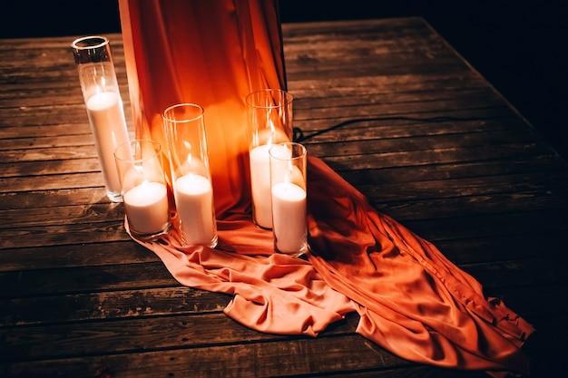Nacht huwelijksceremonie. bruiloft is versierd met een boog in de avond. krans van gloeilampen. kaarsen in glazen kolven.