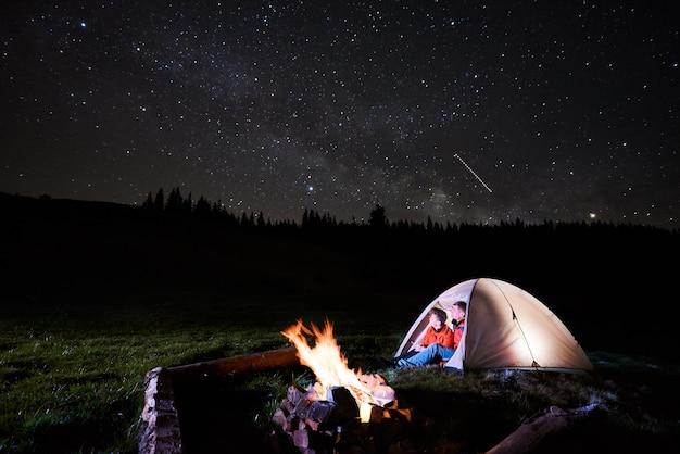 Nacht kamperen in de bergen. romantische paartoeristen die in de verlichte tent dichtbij kampvuur zitten en bij nacht mooie sterrenhemel bekijken