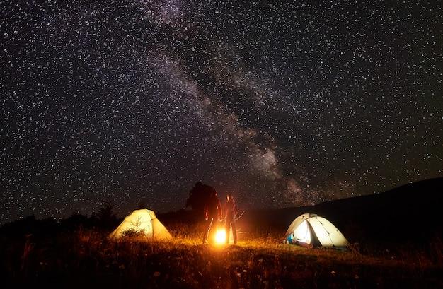 Nacht kamperen in de bergen. silhouetten van man en vrouw die voor glanzende tenten staan, hand in hand onder een verbazingwekkende donkere sterrenhemel en de melkweg