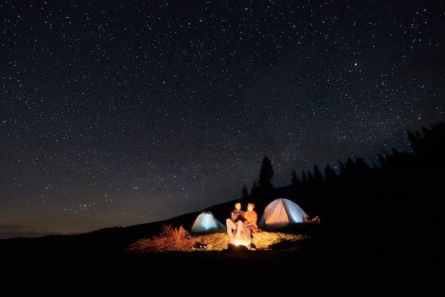 Nacht kamperen. paartoeristen die bij een kampvuur dichtbij twee verlichte tenten onder nachtsterrige hemel zitten