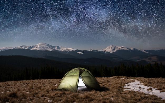Nacht kamperen. verlichte toeristentent onder mooie nachthemel vol sterren en melkweg