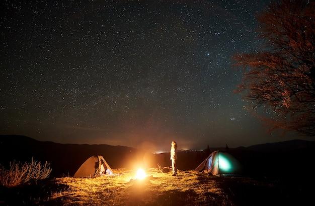Nacht kamperen. wandelaar rusten in de buurt van kampvuur onder de sterrenhemel