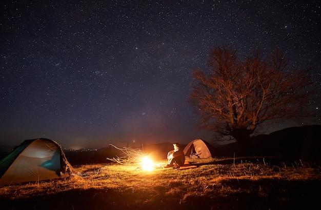 Nacht kamperen. wandelaars die dichtbij kampvuur onder de sterrenhemel rusten