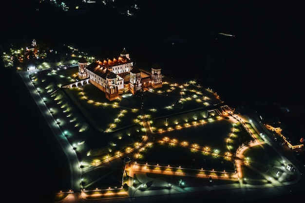 Nacht mir kasteel met torenspitsen in de buurt van het bovenaanzicht van het meer in wit-rusland in de buurt van de stad mir.