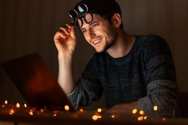 Nacht portret van jonge man aan het werk laptop thuis.
