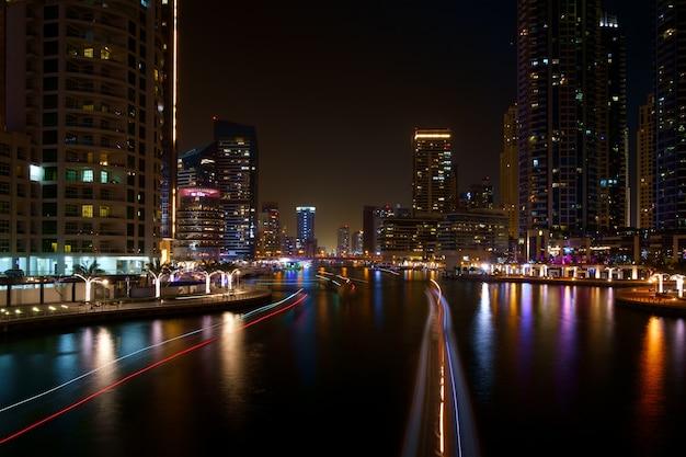 Nacht rivierverkeer lange tracers in het centrum van dubai, verenigde arabische emiraten langs een rivier van de stad met kleurrijke reflecties
