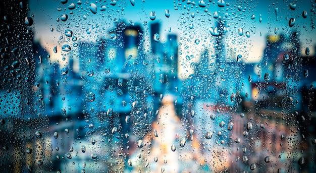 Nacht stadslichten door raam met regenwater en druppels.