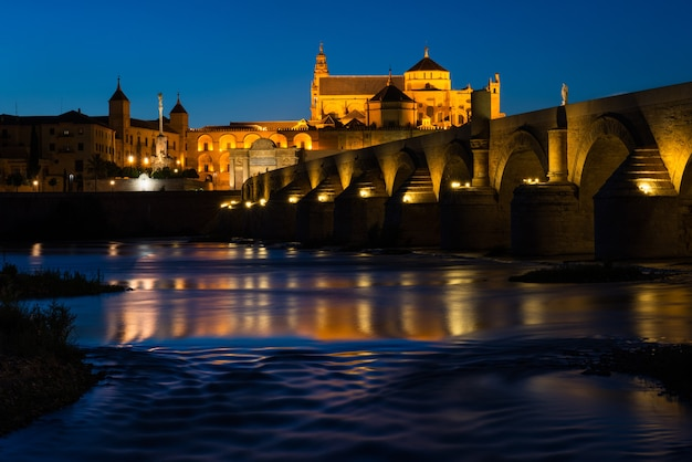 Nacht uitzicht op de beroemde romeinse brug over de rivier de guadalquivir en de moskee-kathedraal 's avonds verlicht in cordoba
