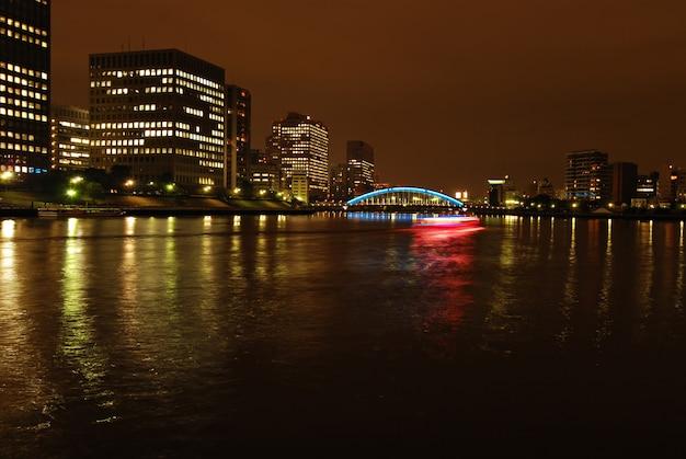 Nacht uitzicht op de stad: sumida-rivier en eitai-brug met bewegend schip in tokio