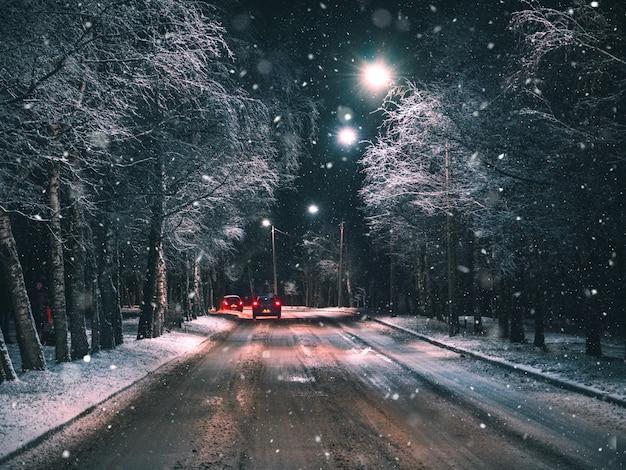 Nacht winter landelijke weg met auto rijden.
