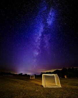 Nachtbeeld van de melkweg met sterrenhemel op voetbalveld. sport concept.