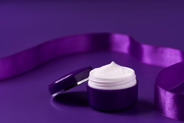 Nachtcosmetica serie van premium hydraterende en voedende cosmetica. plastic potten nachtcosmetica op een paarse achtergrond.