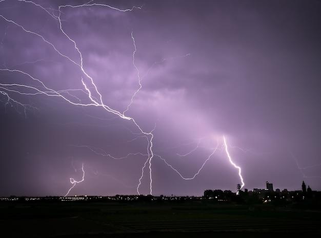 Nachtelijke elektrische storm met blikseminslagen over het silhouet van de stad