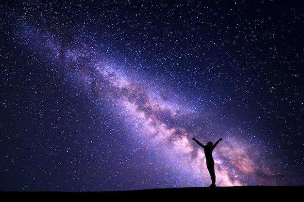 Nachtelijke hemel met melkweg en silhouet van een gelukkige vrouw