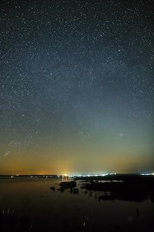 Nachtelijke hemel met sterren boven de rivier tijdens de lentevloed. uitzicht op de sterrenhemel.