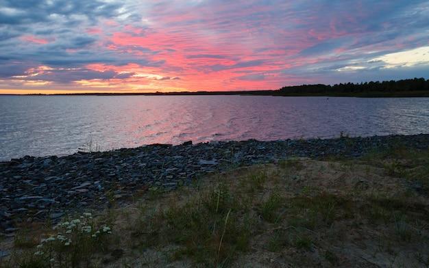 Nachtelijke hemel met wolken, verlicht door de zon, aan de baai (finland, pooldag)