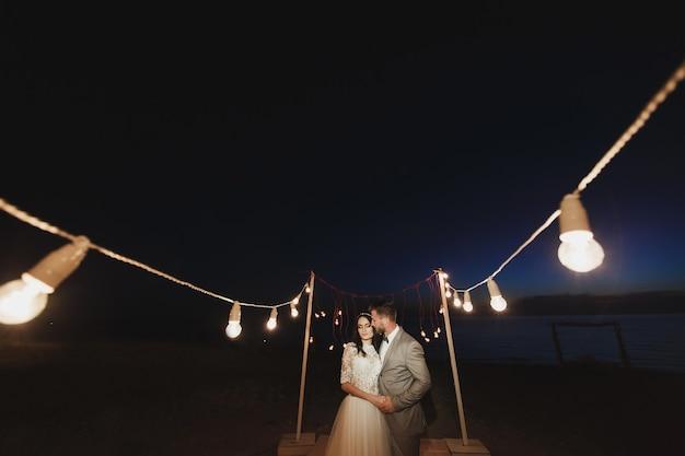 Nachtelijke huwelijksceremonie. de bruid en bruidegom knuffelen.